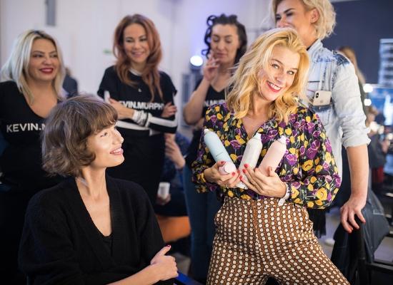 Kobieta, która stoi za włosami modelek na pokazie Dawida Wolińskiego