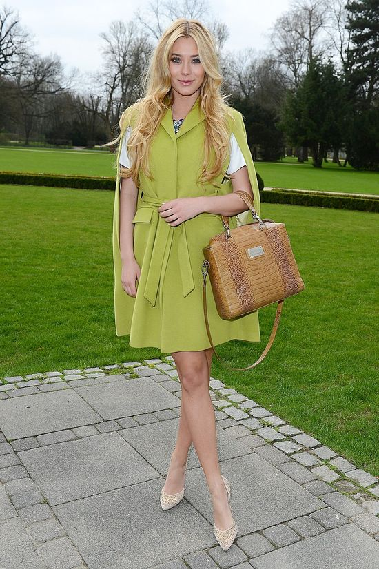 Marcelina Zawadzka w zielonym płaszczyku i białej sukience